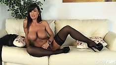 Lisa Ann poses seductively in a pair of stockings and high heels
