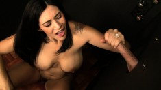 Big tit brunette Raylene fingers her clit while eating cock in a glory hole